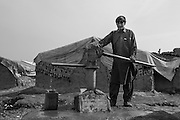 A young man pumps water at the IDP Charahi Qambar refugee camp.