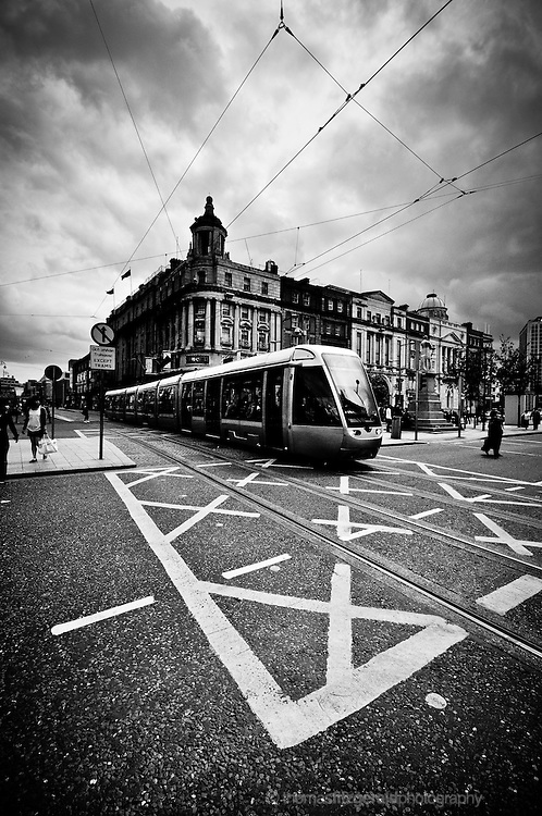 Dublin City, Ireland: The Luas Tram crosses an intersection on the capital city's main street: O'Connell Street. Portrait Orientation Black and White Image.<br />