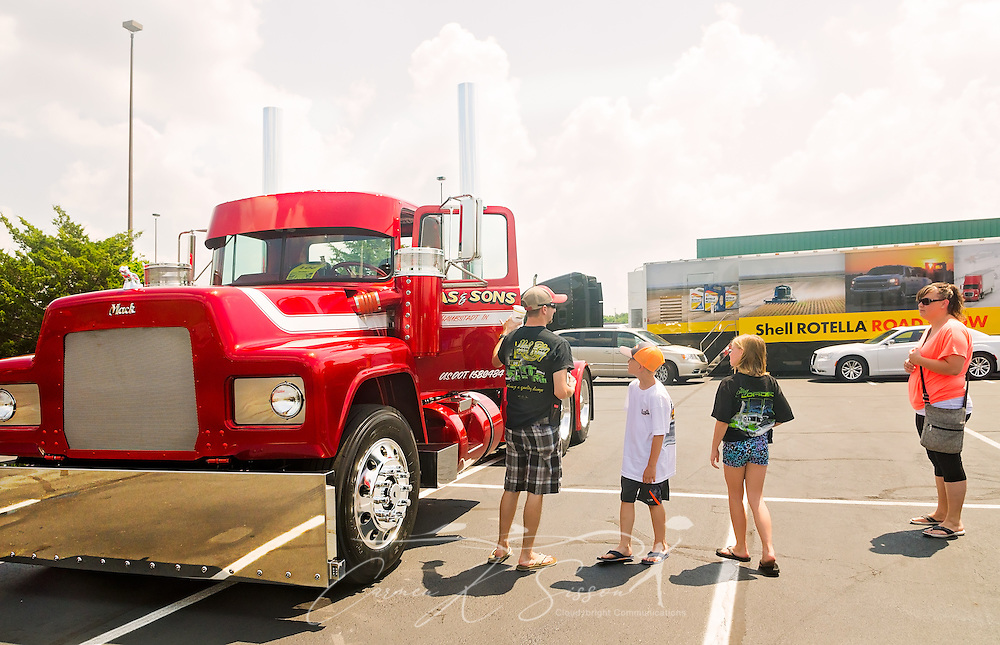 Truck enthusiasts inspect a 1991 Mack RD686, restored by Dickerson Custom Trucks, at the 34th annual Shell Rotella SuperRigs truck beauty contest, June 11, 2016, in Joplin, Missouri. SuperRigs, organized by Shell Oil Company, is an annual beauty contest for working trucks. Approximately 89 trucks entered this year's competition. The truck received the SuperRigs show truck award. (Photo by Carmen K. Sisson/Cloudybright)