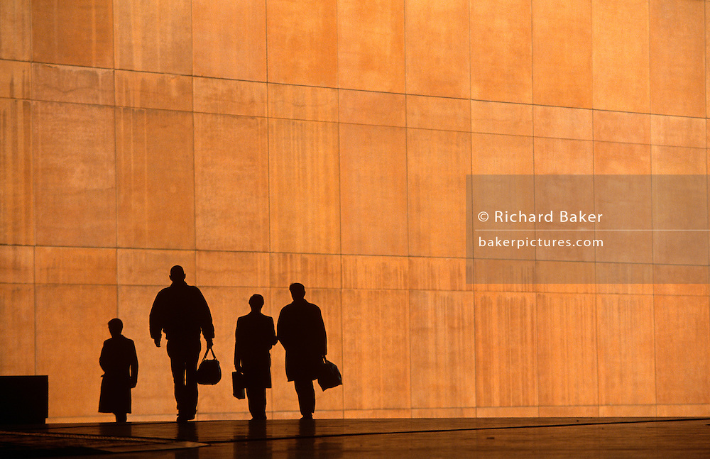 We see four office workers silhouetted against the large orange wall of the Credit Lyonnais Bank at Broadgate in the City of London, UK. Several figures who are also reduced to black shapes and without detail that may identify them or their clothes, are hurrying in different directions, carrying a bag or briefcase but the feeling of rushing business is seen and their scale is ambiguous becase we don't know how close or far away they are from each other. This is due to telephoto lens forshortening. Some therefore look giants and some appear tiny. Broadgate Estate is a large, 32 acre (129,000 m²) office and retail estate in the City of London, owned by British Land and managed by Broadgate Estates. It was originally built by Rosehaugh and was the largest office development in London until the arrival of Canary Wharf in the early 1990s..