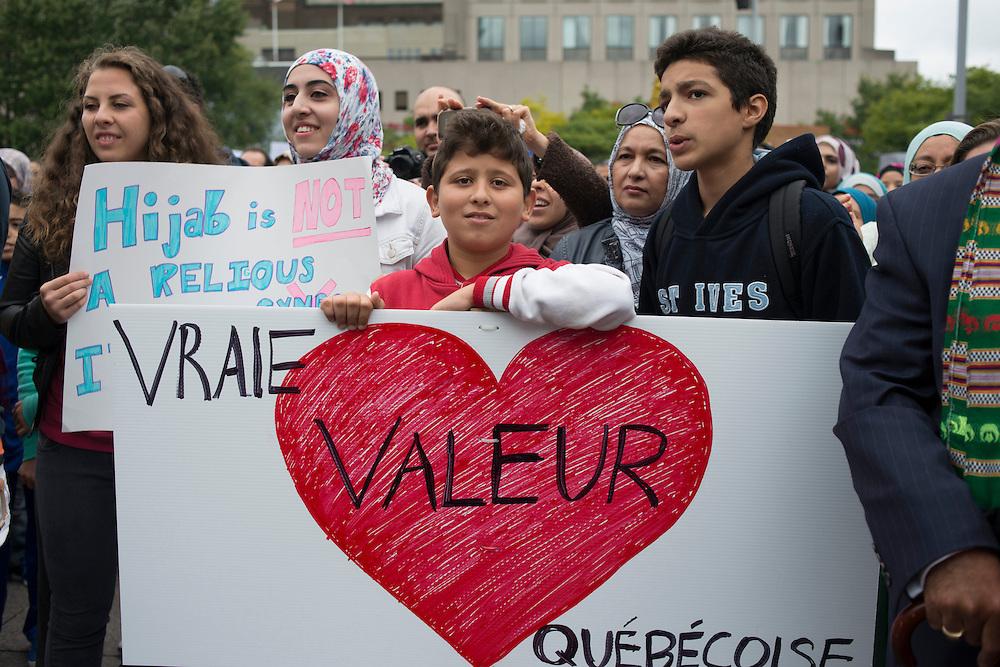 Montr&eacute;al, Canada, le 14 septembre 2013 des milliers de Qu&eacute;b&eacute;coisde communaut&eacute;s et de religions diff&eacute;rentes protestent contre l&rsquo;application de la Charte des valeurs qu&eacute;b&eacute;coises qui interdit aux employ&eacute;s de la fonction publique le port de signes religieux ostentatoires comme le hijab ou la Kippa.<br /> The 14th september 2013, in Montr&eacute;al Canada,  in the first mass action triggered by the proposal, thousands of protesters marched through downtown Montreal to call on the Parti Qu&eacute;b&eacute;cois government of Premier Pauline Marois to withdraw the charter.<br /> Young protesters listen speakers addressing th crowd and stand in front of their sign which means: &quot; Love is a true Quebec value&quot;.