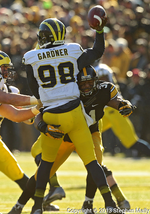 November 23 2013: Iowa Hawkeyes linebacker Anthony Hitchens (31) hits Michigan Wolverines quarterback Devin Gardner (98) as he releases the ball during the fourth quarter of the NCAA football game between the Michigan Wolverines and the Iowa Hawkeyes at Kinnick Stadium in Iowa City, Iowa on November 23, 2013. Iowa defeated Michigan 27-24. Iowa defeated Michigan 24-21.
