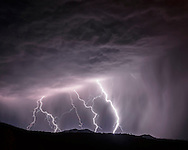 Cloud-to-ground lightning, multiple bolts beyond forest ridge at night, © 2015 David A. Ponton