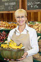 Portrait of a happy senior female employee carrying bananas in farmer's market