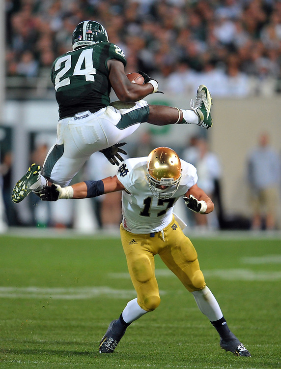 Michigan State Spartans running back Le'Veon Bell (24) leaps over safety Zeke Motta (17) in the third quarter.
