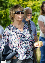 © Licensed to London News Pictures. 16/06/2017. LONDON, UK.  A woman holds a candle at The Great Get Together. Neighbours and friends of Jo Cox attend The Great Get Together near Hermitage Moorings in Wapping to pay tribute and celebrate Jo's call that more unites us than divides us on the anniversary of her death. Jo Cox lived on a house boat in Wapping with her husband Brendan Cox and two children. Photo credit: Vickie Flores/LNP