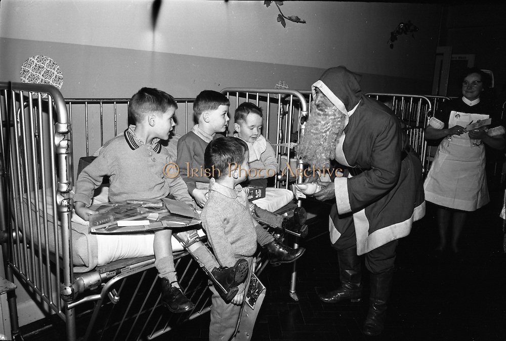 Prescott's Party for Children at St. Mary's Hospital, Baldoyle..1964..16.12.1964..12.16.1964..16th December 1964..At St Mary's Hospital in Baldoyle,Dublin, Prescotts Cleaners and Dyers sponsored a party for the disabled children who are resident there...Picture shows Santa Claus, assisted by the nurses, distributing presents to the children of St Mary's Hospital in Baldoyle, Dublin.