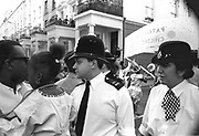 Police man and police woman walking through the crowd, Notting Hill Carnival, London, 1989