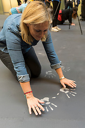 "© Licensed to London News Pictures. 01/10/2018. LONDON, UK. A visitor leaves hand prints on the heat-sensitive floor. Unveiling of the this year's Hyundai Commission by Cuban artist and activist Tania Bruguera at Tate Modern.  The work is called ""an ever-increasing figure"", which represents the scale of mass migration and the risks involved.  Visitors are invited to interact with the work which comprises a heat-sensitive floor, which includes a portrait of a person's face beneath, combined with low frequency sounds.  The work is on display 2 October to 24 February 2019..  Photo credit: Stephen Chung/LNP"
