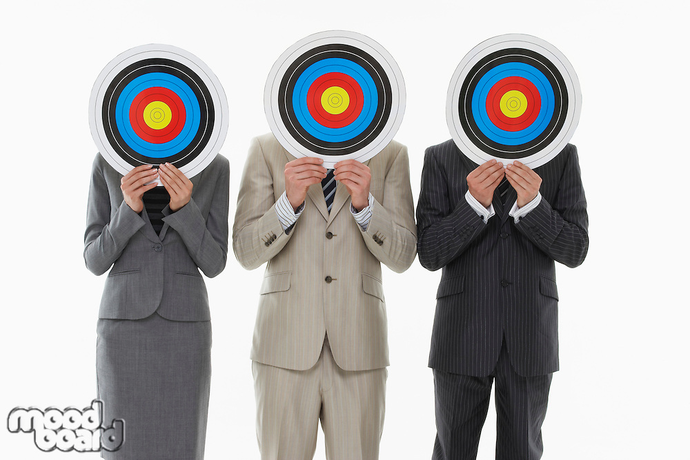 Three business people holding targets in front of faces against white background
