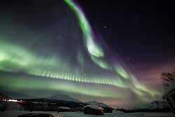 © Licensed to London News Pictures Ltd.  Breivikeidet, Norway. Aurora dramatically lights up the sky over the town of Breivikeidet, Norway, in temperatures of -25 degrees Celsius. Caused by a coronal hole on the sun releasing solar winds a few nights ago which hit our magnetic field on 31st Jan. Photo Credit: Clare Forster/LNP