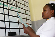 Sister Judith Kyarisiima using the white board at Mbarara Hospital, Uganda.<br /> <br /> RCOG volunteer, Doctor Kim MacLeod  suggested using red stickers to mark patient files and she put up a white board so that we could quickly track the situation on the wards. These systems are helping to monitor high risk mothers who are critically ill.