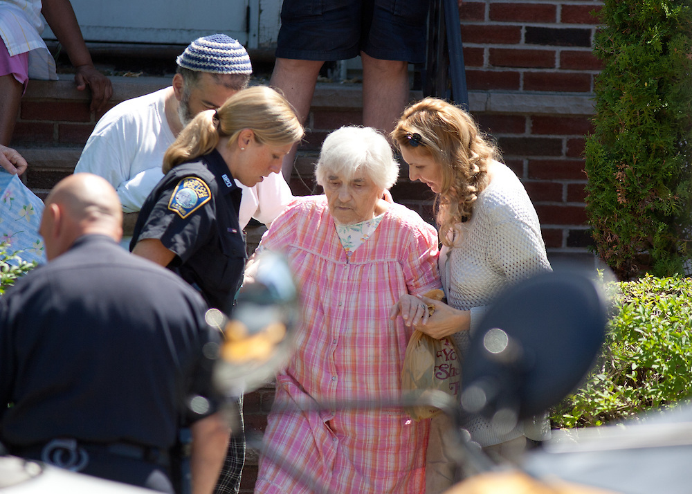 Boston, MA 08/10/2011.An elderly resident is evacuated from the scene of a fatal shooting at 17 Ledgemere Rd. in Brighton on Wednesday morning..Alex Jones / www.alexjonesphoto.com