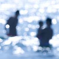 People in the blue sea as silhouettes with sparkling water in the summer