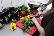 cook cuts fresh vegetables including eggplant, peppers, and green leaves