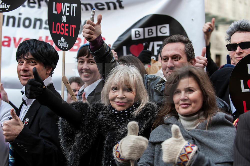 """© Licensed to London News Pictures. 23/11/2015. LONDON, UK. Former Doctor Who girls, Katy Manning and Sophie Aldred  (centre), stand with fans of Doctor Who known as """"Whovians"""" and other supporters of the BBC gathered outside Broadcasting House in central London to oppose the threat of 20% government cuts to the Corporation which has brought shows such as Dr Who since 1922. Photo credit : Stephen Chung/LNP"""