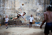 A moment of the game on a pitch next to a landfill. Yangon, Myanmar.