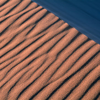 Namibia, Namib Desert, Setting sun lights wind-blown sand along dunes near coastal city of Walvis Bay