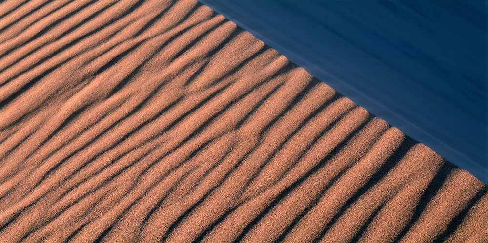 Namibia, Namib Desert, Setting sun lights wind-blown sand along dunes near coastal city of Walvis Bay