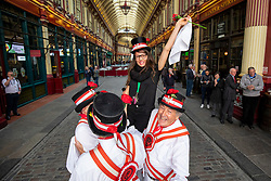 © Licensed to London News Pictures. 23/04/2018. London, UK. The Ewell St Mary's Morris Men lift a member of the public into the air during a performance at a St George's Day celebration in Leadenhall Market. Photo credit: Rob Pinney/LNP