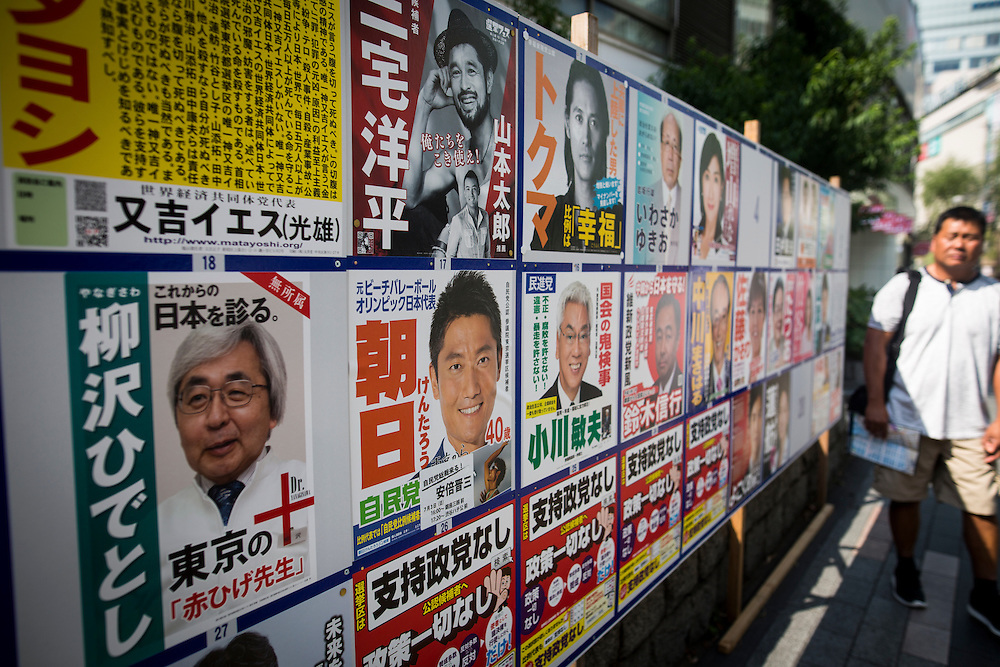TOKYO, JAPAN - JULY 03 : A man walks past at campaign posters with pictures of candidates for the 2016 Upper House election in Tokyo, Japan, on Monday, July 4, 2016. Japanese voters will fill in their ballots next week, July 10, 2016 for the Upper House election. (Photo by Richard Atrero de Guzman/NurPhoto)