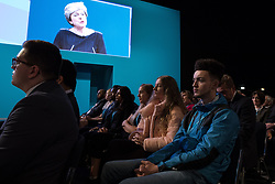 © Licensed to London News Pictures . 04/10/2017. Manchester, UK. Delegates watch Prime Minister THERESA MAY deliver her keynote speech in the conference hall , on the fourth and final day of the Conservative Party Conference at the Manchester Central Convention Centre . Photo credit: Joel Goodman/LNP