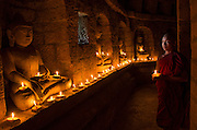 Buddhist monks lighting candles, Mrauk U, Myanmar