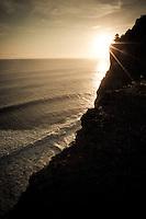 The sun sets over the Indian Ocean near Uluwatu Temple, Bali, Indonesia.