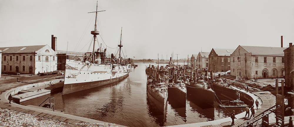 Torpedo boats and cruiser or battleship in the wet dock, Norfolk Navy Yard, Va. (Hampton Roads) circa 1905