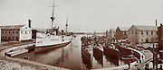 Torpedo boats and cruiser or battleship in the wet dock, Norfolk Navy Yard, Va. (Hampton Roads) circa 1905