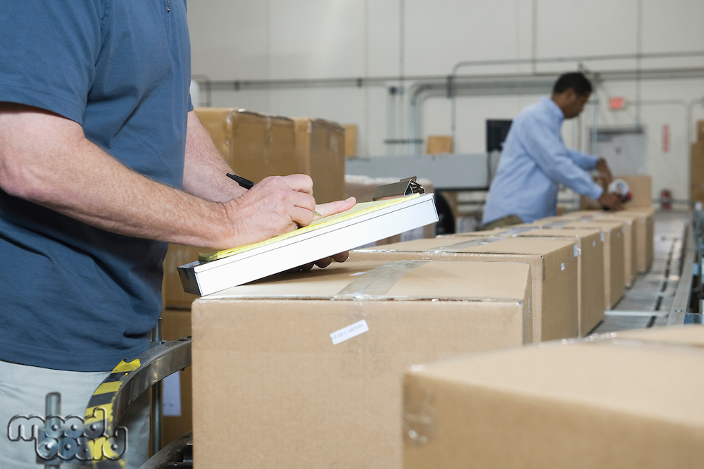 Men working in distribution warehouse close-up