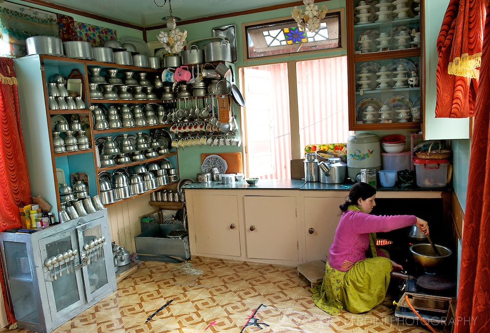 A woman prepares a vegetable curry in his large and tidy kitchen. Dal Lake Srinagar. Kashmir. India