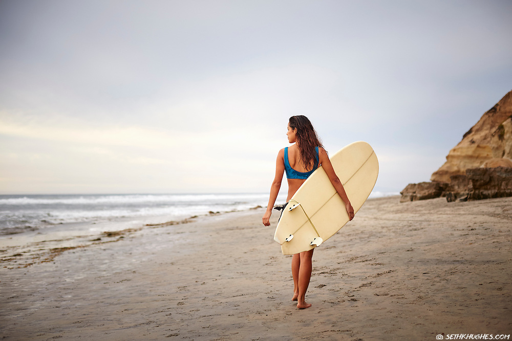 A young woman walks down the beach holding a surfboard in San Diego, California.