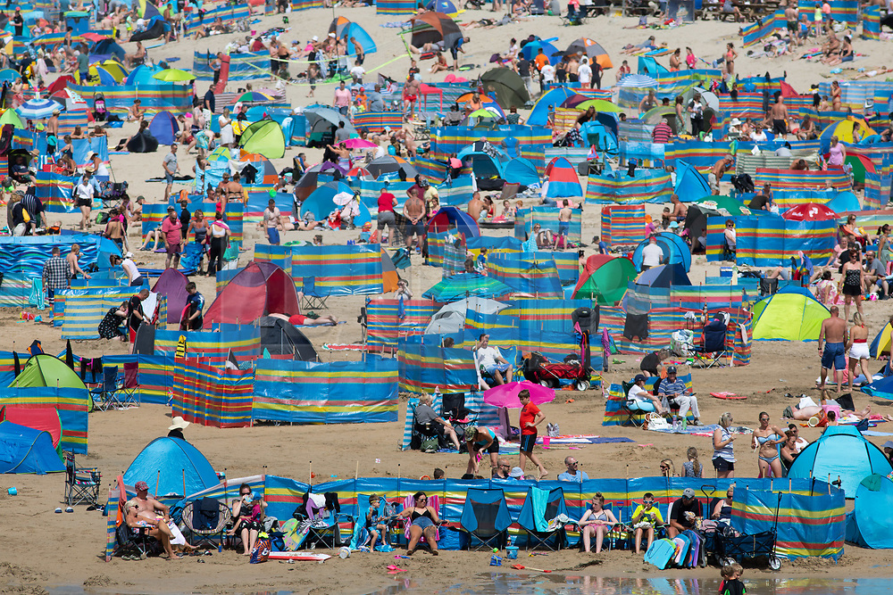 © Licensed to London News Pictures. 09/08/2018. Perranporth, UK. Tourists enjoy the hot weather on Perranporth beach during one of the busiest weeks of the year for the beach. Photo credit : Tom Nicholson/LNP