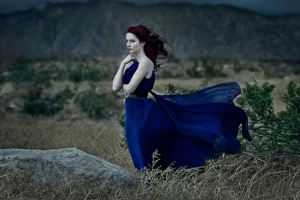A girl in a blue dress standing alone in a desert