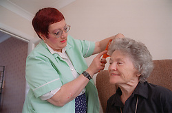 Carer combing elderly woman's hair,