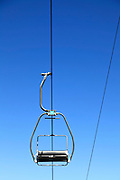 empty ski lift seat against blue sky