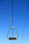 empty ski lift seat against blue sky