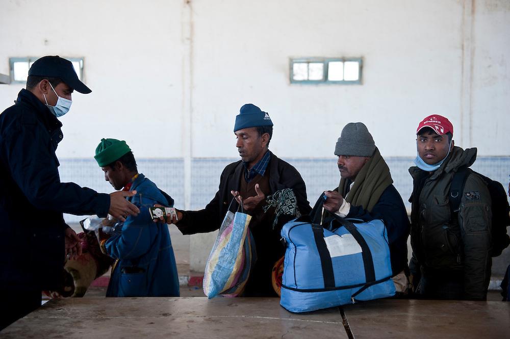 Les réfugiés présentent leur Passeports aux autorités Tunisiennes et leurs bagages sont inspectés, poste frontière de Ras Jedir. Plus de 140 000 réfugiés ont déjà quitté la Libye par la Tunisie ou l'Egypte et des milliers continuent d'arriver chaque jours. Mercredi 2 Mars 2011, poste frontière de Ras Jedir, Tunisie..© Benjamin Girette / AP