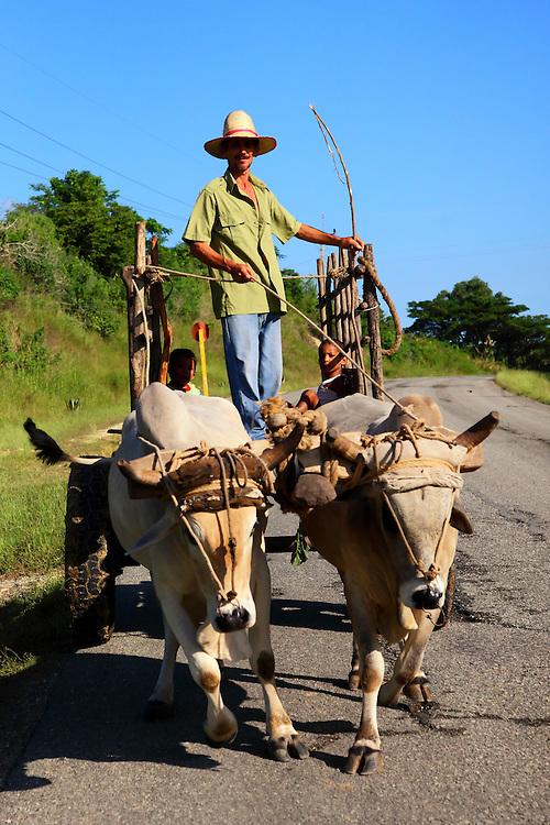 A farmer and his children driving an ox-cart near Sevilla Arriba, Granma Province, Cuba.