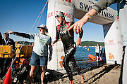 Professional Ironman competitor John Flanagan turns out of the water and gets guided to the first transition zone by volunteer workers...