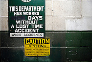 Signage from a warehouse in Chicago saying to avoid accidents and caution against spitting.
