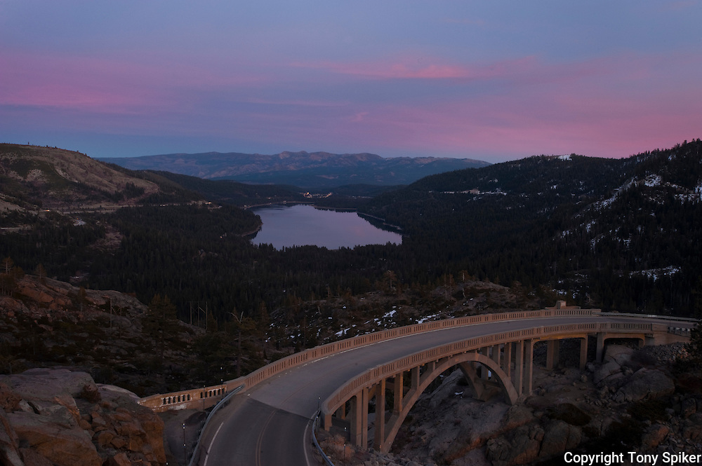 """Donner Lake Sunset 3"" - A photograph of the sun setting over Donner Lake with Rainbow Bridge in the foreground."