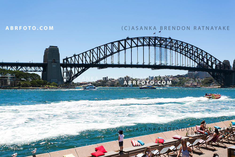People relax while dining along the fringe of Sydney Harbour in Circular Quay with the Sydney Harbour Bridge in the background