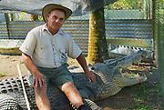 JOHNSTONE RIVER, AUSTRALIA - NOVEMBER 06, 2007: Crocodile farmer Mick Tabone sits on the biggest monster reptile kept behind fence in Australia in Jonston River, Australia.