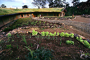 Peter Menzel's first rammed earth passive solar home, with sod roof, in Napa, California, USA. Vegetable garden is planted in front.