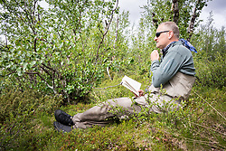 3 July 2017, Tjuonajokk, Lapland, Sweden: Andi from Switzerland contemplates over a book by the Taivek rapid. Tjuonajokk is an old Sami village by the River Kaitum in northern Sweden, now used as a fishing lodge for flyfishers from across the world. The camp is part of Fishyourdream. Here, Andi from Switzerland with a medium-sized Grayling.