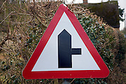 Red triangle road sign showing turning right