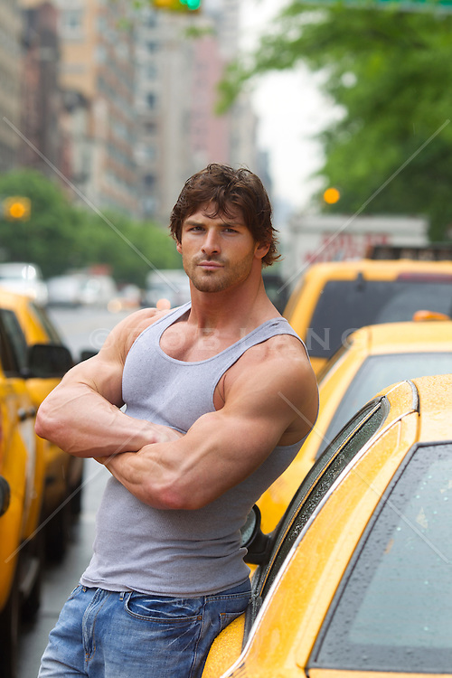 handsome rugged man standing by New York City cabs