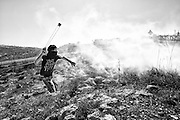 A Palestinian youth hurls a stone with a sling at Israeli forces. Bil'in. Mar. 4, 2011. West Bank, Palestine.
